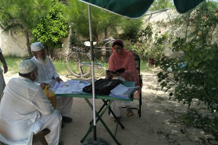 Anum Noureen a female plant doctor in Pakistan advising two male farmers at a plant clinic